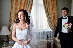 Hübscher Bräutigam sieht zuerst die Schönheitsbraut morgens Stockfotos