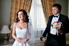 Hübscher Bräutigam sieht zuerst die Schönheitsbraut morgens Lizenzfreie Stockfotografie