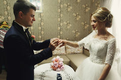 Hübscher Bräutigam und schöne blonde Braut, die goldenes wedd austauscht Stockfotografie