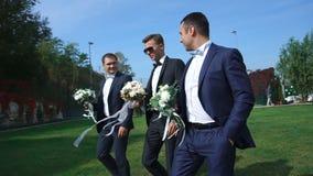 Hübscher Bräutigam und seine Trauzeugen mit Hochzeitsblumensträußen gehen entlang den Garten und der Unterhaltung stock footage