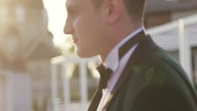 Hübscher Brünettebräutigam im schwarzen Hochzeitsanzug und in der Fliege kommt zur schönen Braut auf und gibt ihr einen Kuss hoch stock footage