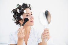 Hübscher Brunette in den Haarrollen, die das Handspiegel und -c$zutreffen halten Lizenzfreies Stockbild