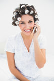 Hübscher Brunette in den Haarrollen am Telefon auf Bett Lizenzfreie Stockbilder