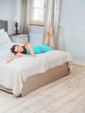 Hübscher Brunette, der auf dem breiten Bett liegt lizenzfreies stockfoto