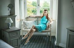 Hübscher Brunette, der auf der Weidenbank sitzt lizenzfreie stockfotografie