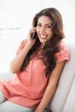 Hübscher Brunette, der auf ihrer Couch bei einem Telefonanruf sitzt Stockfotografie