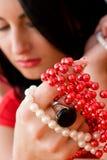 Hübscher Brunette, der die roten und weißen Korne anhält Stockbild