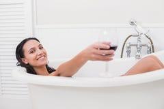 Hübscher Brunette, der ein Bad mit Glas Wein nimmt Lizenzfreies Stockfoto