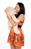 Hübscher Brunette, der einen Teddybären umarmt Lizenzfreie Stockfotos