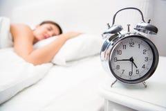 Hübscher Brunette, der im Bett mit Wecker schläft Lizenzfreie Stockfotos