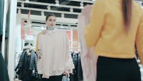 Hübscher Brunette, der zwischen zwei Blusen wählt Junge lächelnde Frau, die Kleidung im Speicher untersucht Spiegel überprüft Art stock footage