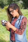 Hübscher Brunette im Park unter Verwendung der Retro- Kamera Stockbilder