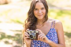 Hübscher Brunette im Park unter Verwendung der Retro- Kamera Lizenzfreie Stockbilder