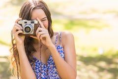 Hübscher Brunette im Park unter Verwendung der Retro- Kamera Stockbild