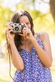 Hübscher Brunette im Park unter Verwendung der Retro- Kamera Stockfotos