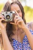 Hübscher Brunette im Park unter Verwendung der Retro- Kamera Stockfotografie