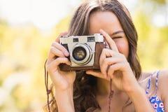 Hübscher Brunette im Park unter Verwendung der Retro- Kamera Lizenzfreies Stockbild