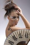 Hübscher Brunette in Japan-Art mit der Hand auf dem Kopf Stockbilder