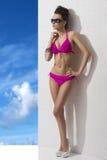 Hübscher Brunette mit Bikini und der Hand auf der Hüfte Lizenzfreies Stockbild