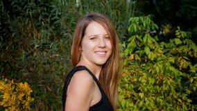 Hübscher Brunette mit dem langen Haar im grünen Park, der die Kamera während Autumn Days aufwirft und betrachtet Lizenzfreie Stockfotografie