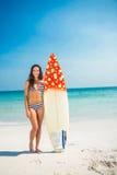 Hübscher Brunette mit einem Surfbrett an einem sonnigen Tag Stockfotografie