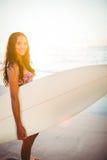 Hübscher Brunette mit einem Surfbrett an einem sonnigen Tag Lizenzfreie Stockfotografie