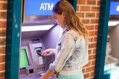 Hübscher Brunettestudent, der Bargeld zurücknimmt Stockbild