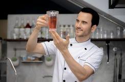 Hübscher Chef in der Uniform, die ein Glas Wasser anhebt Lizenzfreie Stockbilder