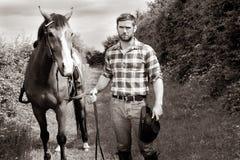 Hübscher Cowboy, Pferdereiter auf Sattel, zu Pferde ADN-Stiefel stockfotografie