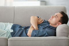 Hübscher deprimierter Mann auf Couch Lizenzfreies Stockfoto