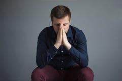 Hübscher deprimierter Mann auf grauem Hintergrund Lizenzfreie Stockfotos