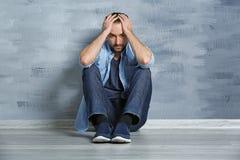 Hübscher deprimierter Mann, der auf Boden sitzt Lizenzfreie Stockfotografie