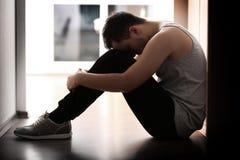Hübscher deprimierter Mann, der auf Boden sitzt Lizenzfreie Stockbilder