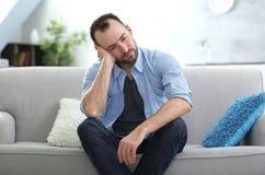 Hübscher deprimierter Mann, der auf Sofa sitzt Lizenzfreie Stockfotos