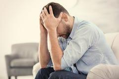 Hübscher deprimierter Mann, der auf Sofa sitzt Lizenzfreies Stockfoto
