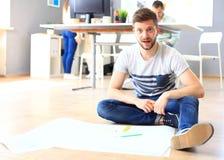 Hübscher Designer sitzen in seinem Büro mit der Kollegediskussion Stockfoto