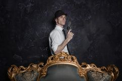 Hübscher Detektiv im Hut, der ein Gewehr in der Dunkelheit hält stockbild