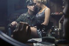 Hübscher deutscher Soldat mit Blondinen auf seinen Knien Stockfotos