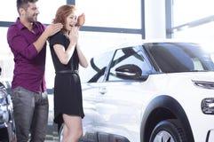 Hübscher Ehemann überraschend seine Frau mit einem Autokauf stockbild