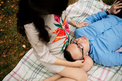 Hübscher Ehemann, der auf dem Bein seiner jungen schwangeren Schönheit im Park liegt Stockfotografie
