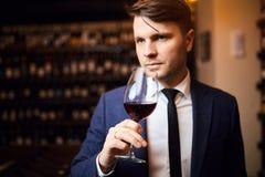 Hübscher ehrfürchtiger Mann genießt, Wein zu trinken stockfotografie