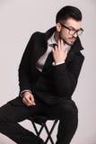 Hübscher eleganter Geschäftsmann, der auf einem Schemel sitzt Stockfotografie