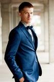 Hübscher eleganter Mann trägt blauen Anzug mit Fliege Stockfotografie