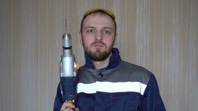 Hübscher Erbauer in der Uniform mit Werkzeuggurt-Holdingbohrgerät Bärtiges Arbeitsbohrgerät des jungen Mannes stock video