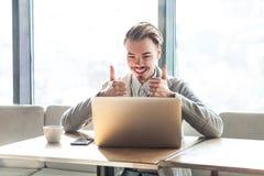 Hübscher erfüllter positiver junger Freiberufler im grauen Blazer sitzen im Café und passen auf Laptop mit toothy Lächeln und dem stockfotografie