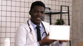 Hübscher ernster afrikanischer Doktor, der Produkt auf Tablettenschirm darstellt Weiße Bildschirmanzeige lizenzfreie stockfotos