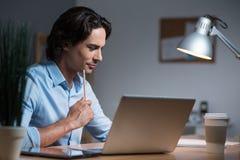 Hübscher ernster junger Mann, der Laptop verwendet Lizenzfreie Stockfotografie