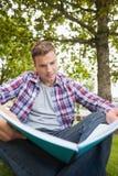 Hübscher ernster Student, der auf dem Grasstudieren sitzt Lizenzfreie Stockfotos