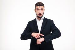 Hübscher erstaunter junger Geschäftsmann mit Bart zeigend auf Uhr Lizenzfreies Stockfoto