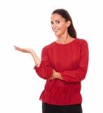Hübscher erwachsener Brunette, der ihre rechte Palme hochhält Stockfoto